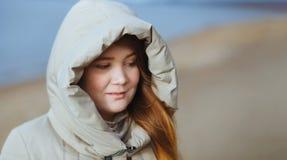 Retrato al aire libre de la muchacha triste de la mujer joven en capilla Flor en la nieve Imagen de archivo libre de regalías
