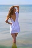 Retrato al aire libre de la mujer bonita joven en el vestido blanco que presenta en el mar Foto de archivo libre de regalías