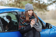 Retrato al aire libre de la mujer caucásica joven, sosteniendo una taza de café para llevar en Forest Park en día frío de la esta Fotografía de archivo