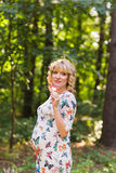 Retrato al aire libre de la mujer embarazada joven que sostiene una piruleta en naturaleza del verano Fotografía de archivo libre de regalías