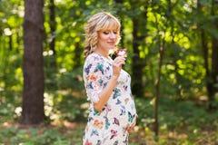 Retrato al aire libre de la mujer embarazada joven que sostiene una piruleta en naturaleza del verano Imagen de archivo