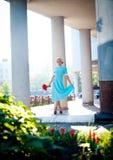 Retrato al aire libre de la mujer joven del pelirrojo hermoso cerca de la columna Ramo de flores rojas fotos de archivo libres de regalías