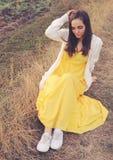 Retrato al aire libre de la mujer joven que se sienta en un campo del deadwood Foto de archivo