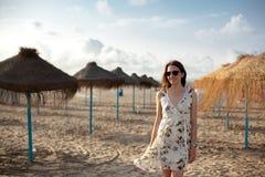 Retrato al aire libre de la mujer morena hermosa de la muchacha en fondo de los paraguas de la paja en la playa en luz de la pues fotografía de archivo libre de regalías
