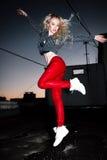 Retrato al aire libre de la señora europea rubia feliz hermosa joven que presenta en la calle en la noche El rojo elegante modelo Foto de archivo libre de regalías