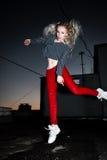 Retrato al aire libre de la señora europea rubia feliz hermosa joven que presenta en la calle en la noche El rojo elegante modelo Fotografía de archivo