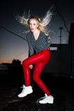 Retrato al aire libre de la señora europea rubia feliz hermosa joven que presenta en la calle en la noche El rojo elegante modelo Fotos de archivo