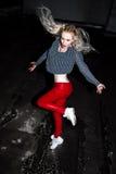 Retrato al aire libre de la señora europea rubia feliz hermosa joven que presenta en la calle en la noche El rojo elegante modelo Fotos de archivo libres de regalías