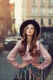 Retrato al aire libre de la señora juguetona de moda hermosa joven que presenta en la calle vieja Sombrero y ropa elegantes que l Foto de archivo