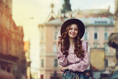 Retrato al aire libre de la señora sonriente de moda hermosa joven que presenta en la calle vieja Sombrero y ropa elegantes que l Fotos de archivo libres de regalías