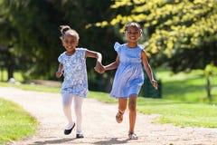 Retrato al aire libre de las hermanas negras jovenes lindas que corren - África Foto de archivo