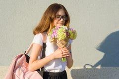 Retrato al aire libre de los vidrios que llevan del adolescente, con el ramo de flores Foto de archivo libre de regalías