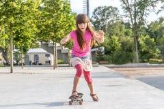 Retrato al aire libre de montar sonriente joven de la muchacha del adolescente skateboar Foto de archivo libre de regalías