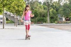 Retrato al aire libre de montar sonriente joven de la muchacha del adolescente skateboar Imagen de archivo