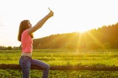 Retrato al aire libre de una muchacha joven del adolescente que usa un smartphone para su blog, y páginas en redes sociales Foto de archivo