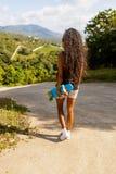 Retrato al aire libre de una muchacha negra adolescente con ska azul del longboard Imagenes de archivo