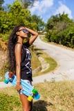 Retrato al aire libre de una muchacha negra adolescente con ska azul del longboard Imagen de archivo libre de regalías