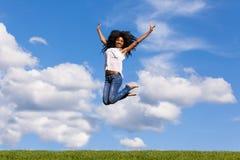 Retrato al aire libre de una muchacha negra adolescente que salta sobre un cielo azul Fotografía de archivo