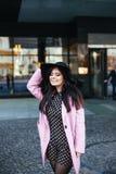 Retrato al aire libre de una mujer de moda hermosa joven que camina en la calle Capa rosada elegante que lleva modelo, negra Foto de archivo