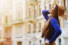 Retrato al aire libre de una mujer sonriente feliz hermosa joven que presenta en la calle Sombrero y ropa elegantes que llevan mo Foto de archivo