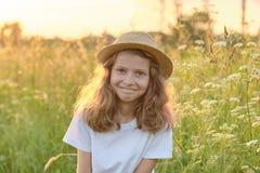 Retrato al aire libre de una pequeña muchacha sonriente en un sombrero en un prado soleado, hora de oro fotos de archivo
