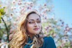 Retrato al aire libre de una señora sonriente feliz hermosa joven que presenta cerca de árbol de la magnolia con las flores Looki Fotografía de archivo