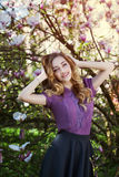 Retrato al aire libre de una señora sonriente feliz hermosa joven que presenta cerca de árbol de la magnolia con las flores Looki Imagen de archivo