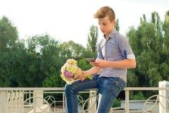 Retrato al aire libre del adolescente con el ramo de flores Imagen de archivo libre de regalías