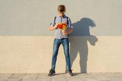 Retrato al aire libre del adolescente con el ramo de flores, fondo gris de la pared, espacio de la copia Foto de archivo libre de regalías