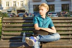 Retrato al aire libre del adolescente de 13, 14 a?os que se sientan en banco en parque de la ciudad imagen de archivo