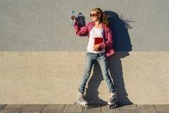 Retrato al aire libre del adolescente sonriente joven de la muchacha con el blad del rodillo Foto de archivo