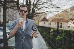 Retrato al aire libre del hombre joven del inconformista que camina en la calle y que usa su smartphone Foto de archivo libre de regalías
