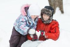 Retrato al aire libre del invierno de dos hermanos que juegan en nieve acumulada por la ventisca con la figura en forma de corazó Fotografía de archivo