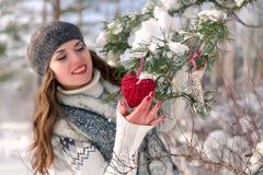 Retrato al aire libre del invierno de una chica joven positiva alegre linda con la decoración roja del corazón en un fondo natura Imagen de archivo