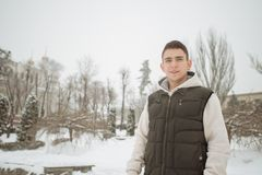 Retrato al aire libre del invierno para el hombre hermoso joven Adolescente hermoso en su chaqueta y chaleco que presentan en una Imágenes de archivo libres de regalías
