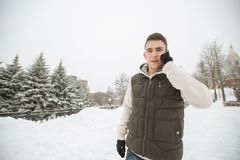 Retrato al aire libre del invierno para el hombre hermoso joven con el teléfono Adolescente hermoso en su chaqueta y chaleco que  Foto de archivo