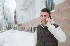 Retrato al aire libre del invierno para el hombre hermoso joven con el teléfono Adolescente hermoso en su chaqueta y chaleco que  Fotos de archivo libres de regalías