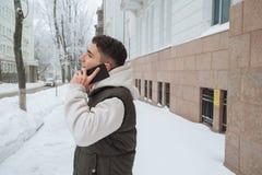 Retrato al aire libre del invierno para el hombre hermoso joven con el teléfono Adolescente hermoso en su chaqueta y chaleco que  Fotos de archivo