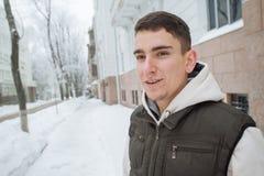 Retrato al aire libre del invierno para el hombre hermoso joven con el teléfono Adolescente hermoso en su chaqueta y chaleco que  Fotografía de archivo libre de regalías