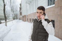 Retrato al aire libre del invierno para el hombre hermoso joven con el teléfono Adolescente hermoso en su chaqueta y chaleco que  Imagen de archivo