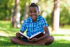 Retrato al aire libre del muchacho del negro del estudiante que lee un libro Imágenes de archivo libres de regalías