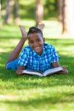 Retrato al aire libre del muchacho del negro del estudiante que lee un libro Fotos de archivo