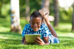 Retrato al aire libre del muchacho del negro del estudiante que usa una tableta táctil Fotos de archivo libres de regalías