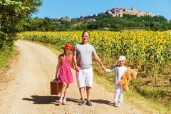 Retrato al aire libre del niños divertidos y el padre que camina abajo del camino Foto de archivo