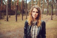 Retrato al aire libre del otoño de la mujer hermosa joven con maquillaje natural en la chaqueta de cuero y la camisa de tela esco imagen de archivo