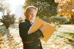 Retrato al aire libre del otoño de un colegial que lee un libro, fondo de árboles amarillos en el parque, muchacho en una chaquet imagen de archivo