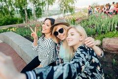Retrato al aire libre del verano de tres muchachas de la diversión de los amigos que toman las fotos con smartphone Fotografía de archivo libre de regalías