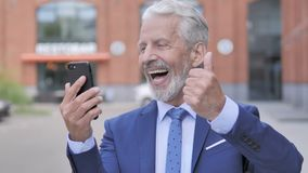 Retrato al aire libre del viejo hombre de negocios Cheering Success en Smartphone metrajes