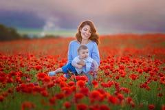 Retrato al aire libre La madre joven y su hija disfrutan del tiempo de la vida junto en un campo de la amapola Concepto de amor y foto de archivo libre de regalías