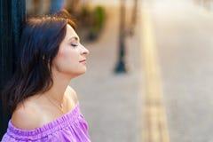 Retrato al aire libre La mujer hermosa joven perdió en pensamiento mientras que visitaba el centro de ciudad en un día soleado, e Imagen de archivo libre de regalías
